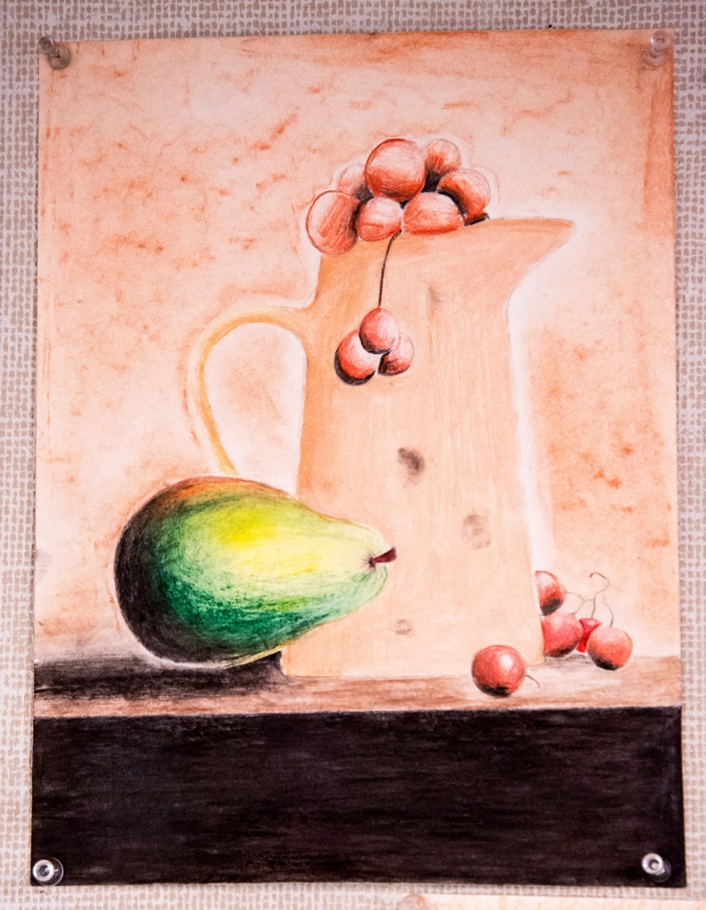 7th grade colored pencil still life of a pitcher with cherries in it, and a pear to the side