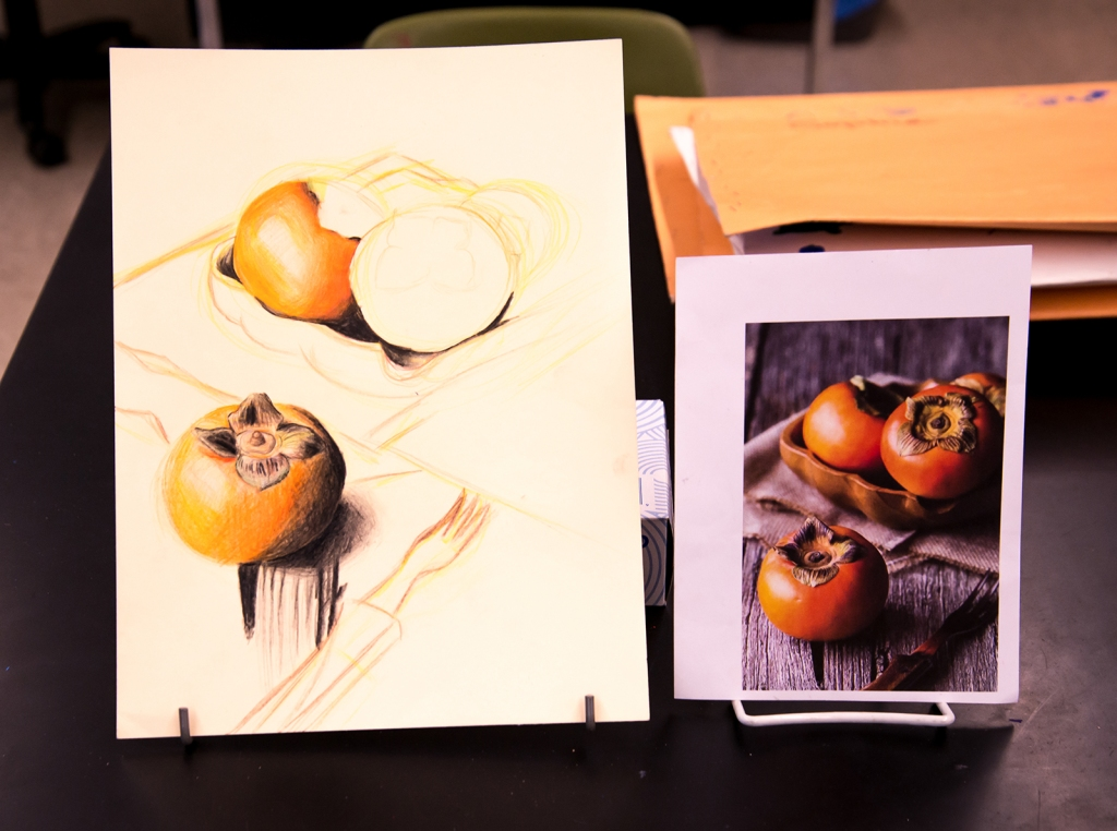 7th grade colored pencil still life in progress of persimmons in a bowl on a table