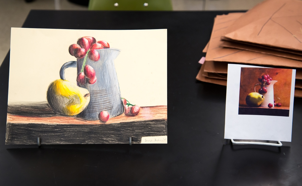 7th grade colored pencil still life in progress, drawing of a pitcher with grapes and a pear on a table
