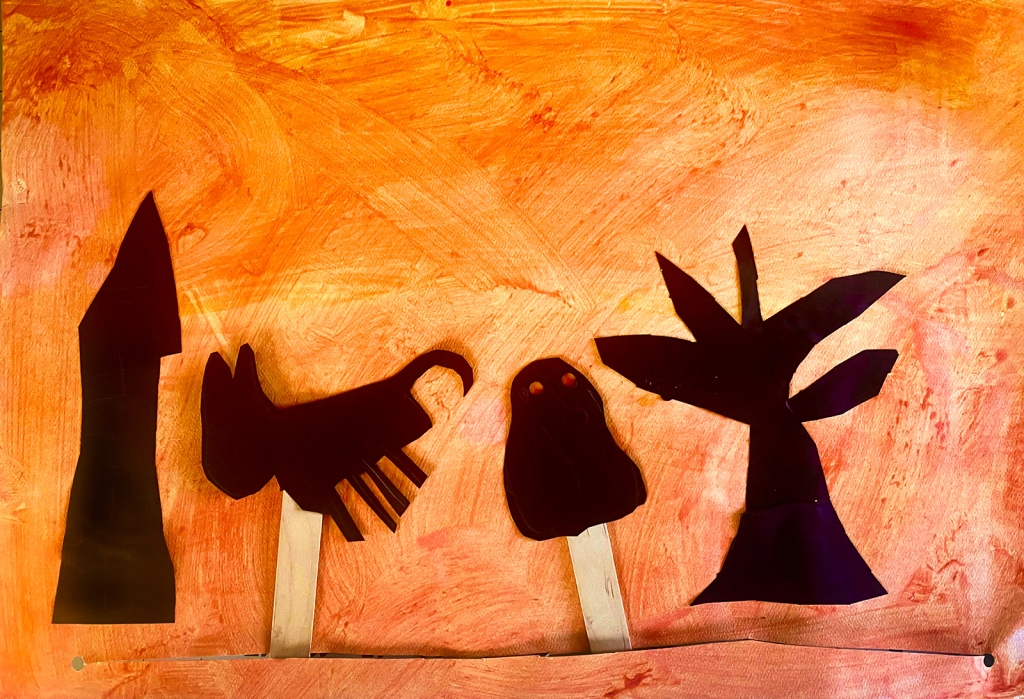 Kindergarten - A student's Halloween shadow puppets of a ghost and black cat with sunset background