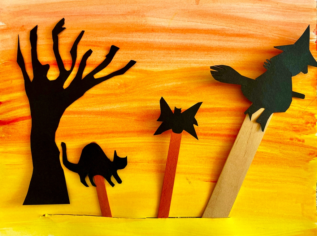 Kindergarten - A student's Halloween shadow puppets of a cat, witch and bat with sunset background
