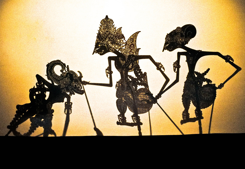 Wayang Kulit shadow puppets against a luminous backlit screen