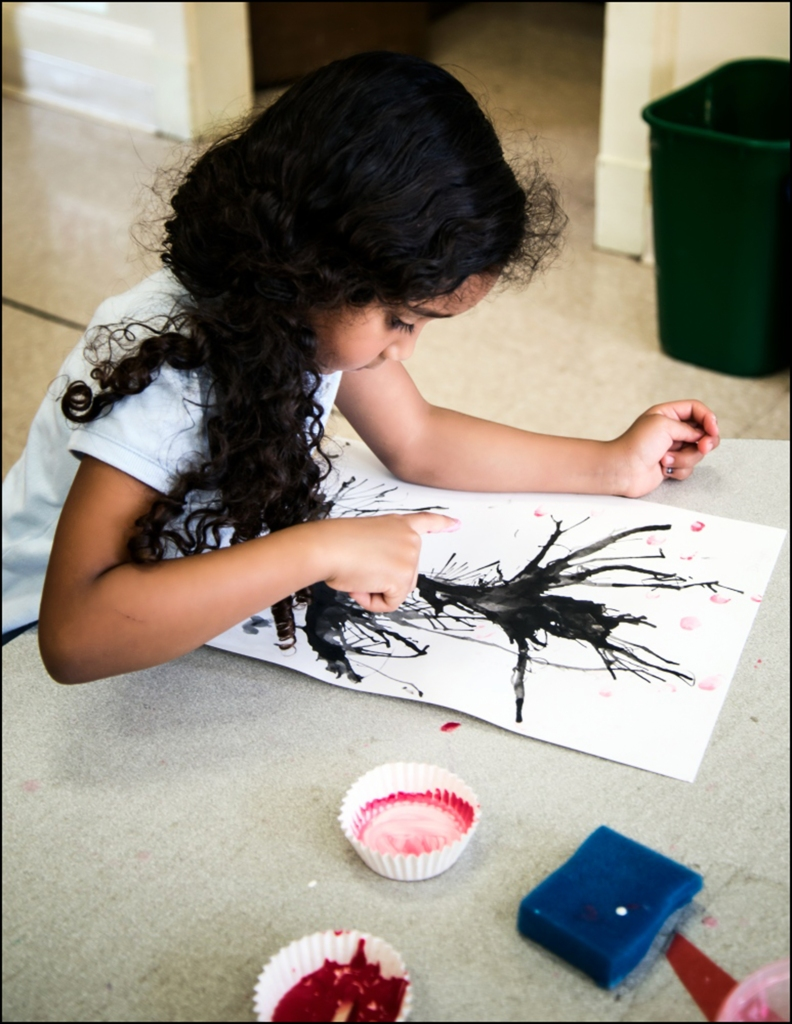1st grade student applying the blossoms with her fingers