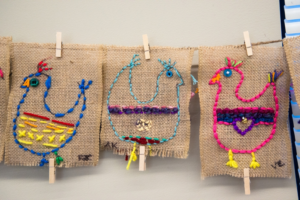 Three examples of 3rd grade students' sewing samplers depicting colorful, whimsical chickens