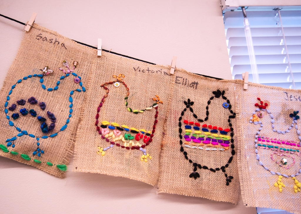 Four examples of 3rd grade students' sewing samplers depicting colorful, whimsical chickens