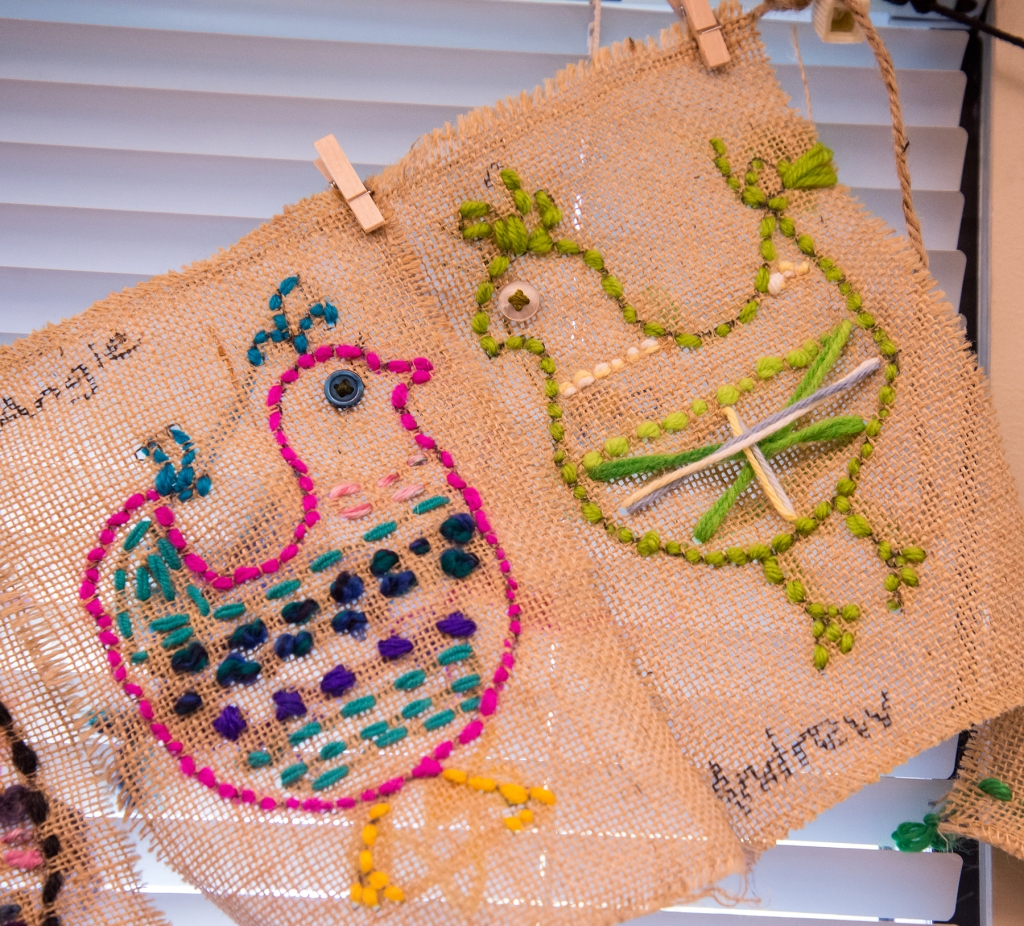 Two examples of 3rd grade students' sewing samplers depicting colorful, whimsical chickens
