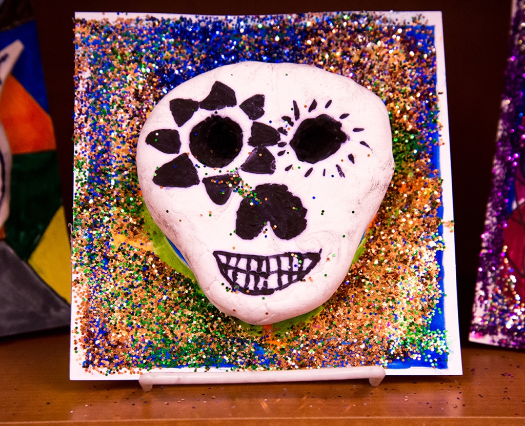 An example of a 4th grade student's clay skull, designed to imitate a Día de los Muertos (Day of the Dead) sugar skull, with a colorful and glittery patterned background