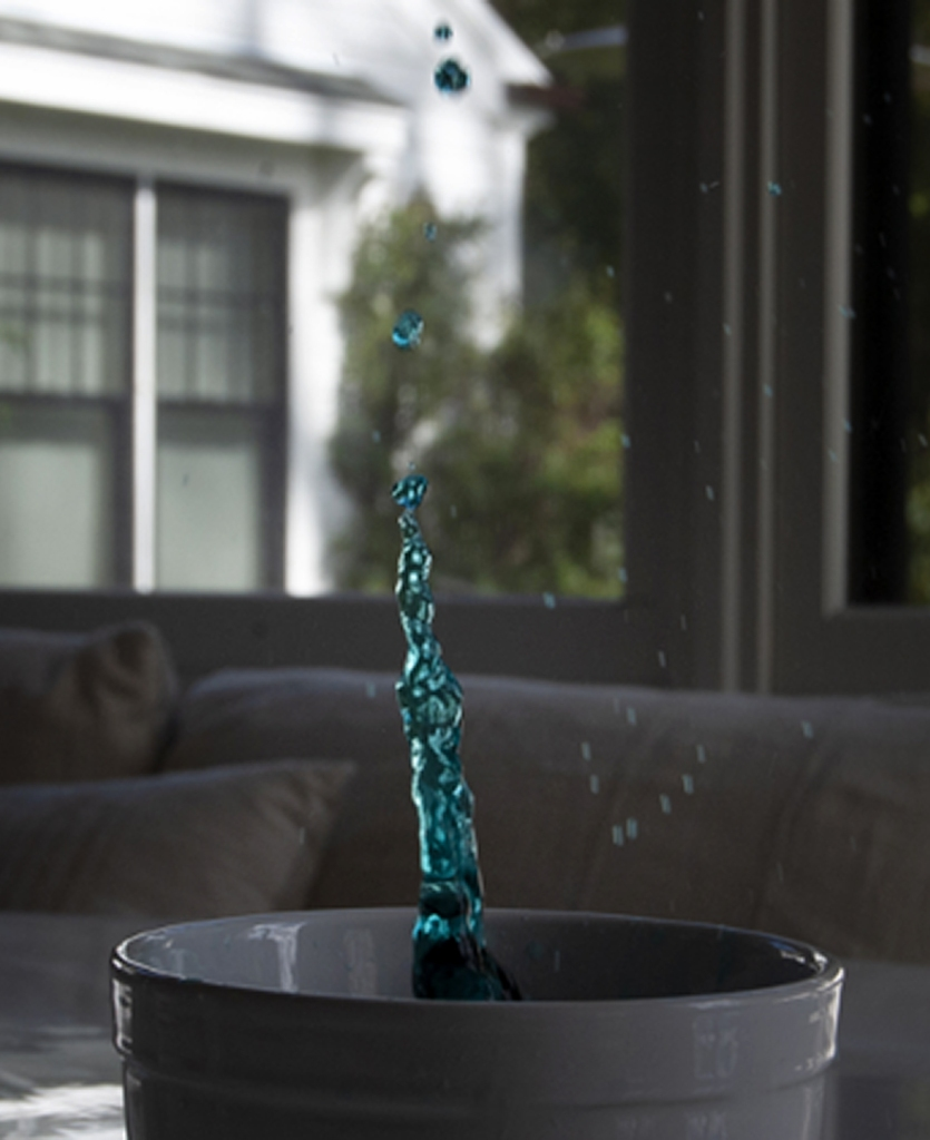 An 8th grade student using shutter speed to capture still motion of a drop of water