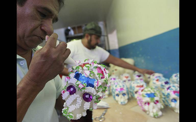 Artisans decorating the sugar skulls with icing