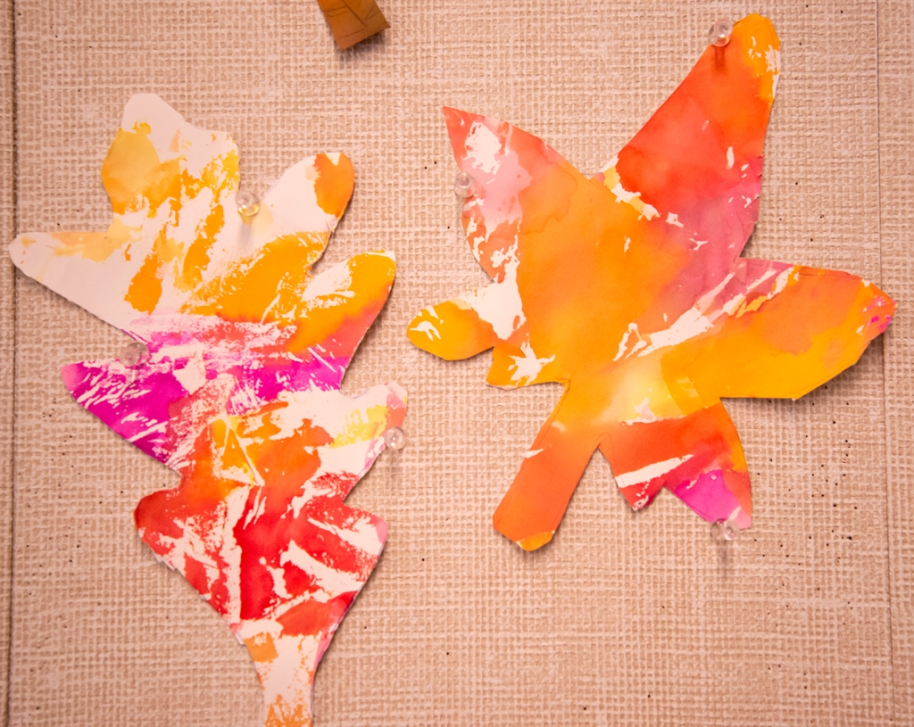 Kindergarten students' autumn leaves, made with warm colored bleeding tissue paper