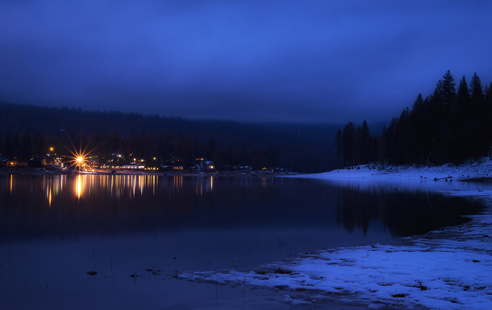 Snowy winter scene, with the lights from homes reflecting on he water's edge, in Bass Lake, California, by Anita Sagastegui