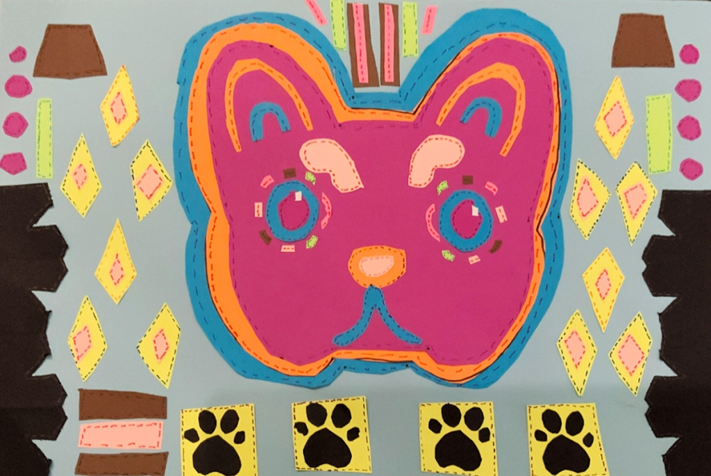 """A 4th grade student Mola, depicting a variously colored cat's head and many layers of patterns, all adorned with """"stitches"""" to look like a real Mola"""
