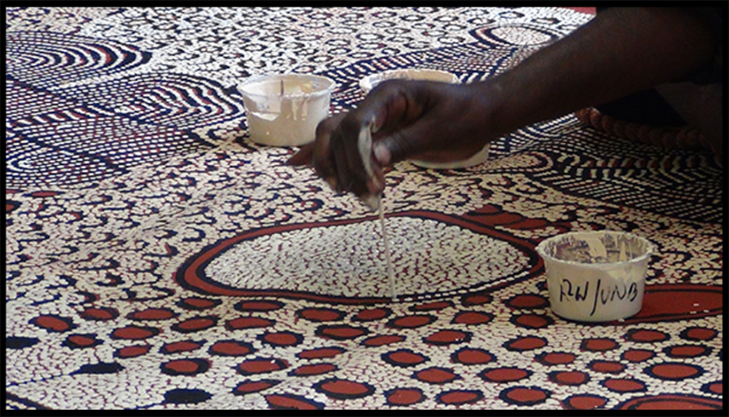A photograph of an Aborigine applying the dots to a painting.