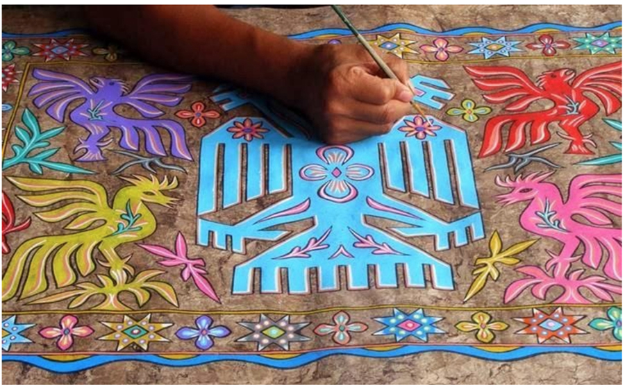 A Mexican artisan working on an Amate painting, depicting traditional subjects, such as birds and flowers, in vibrant colors on Amate bark paper.
