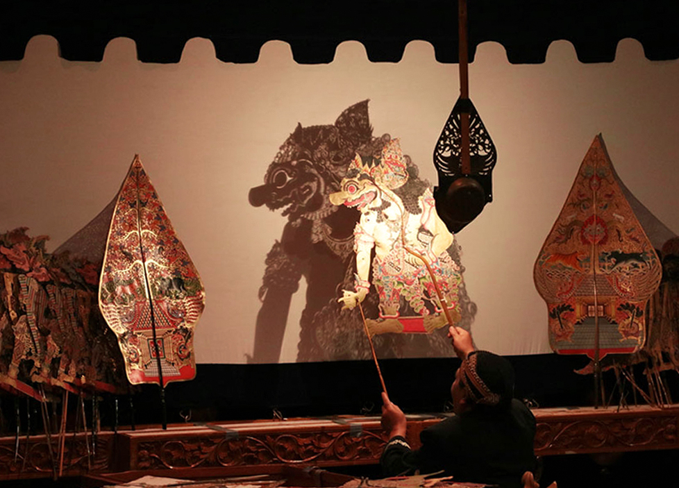 A photographic example of Wayang Kulit in action, with the puppeteer behind the screen holding the puppet by rods attached to the puppet's wrists and head.
