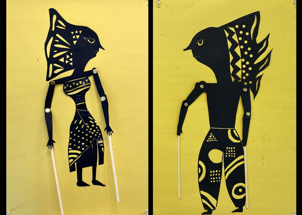 An 8th grade student's paired Wayang Kulit puppets. The puppets are made of black paper and set against a bright yellow background to look like shadow puppets. They are intricately perforated to create elaborate patterns within the costume of each puppet, as well as to express each puppet's features. Their arms are joined with brass fasteners at the elbow and shoulder, manipulated at the hands by sticks