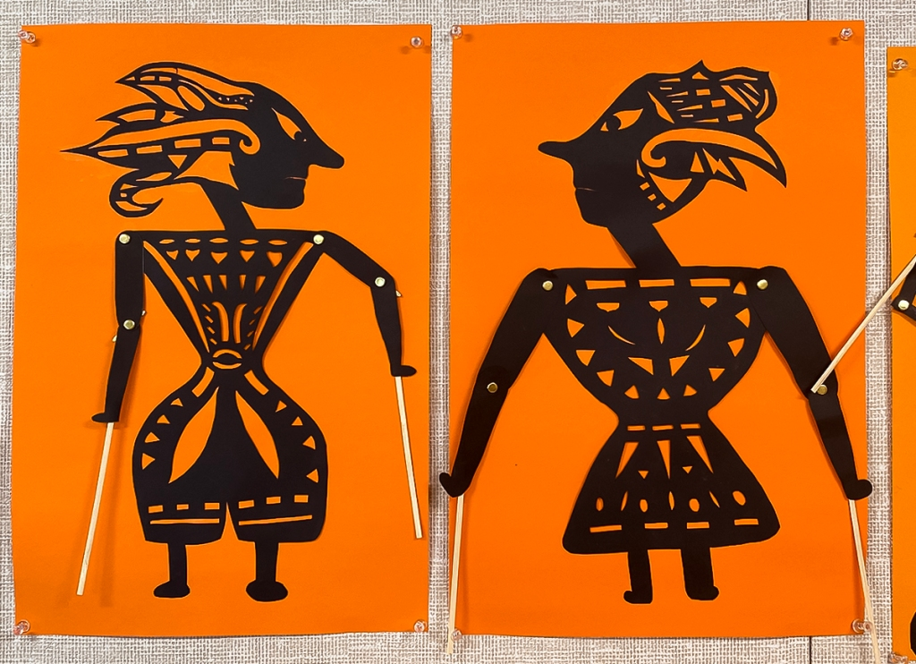 An 8th grade student's paired Wayang Kulit puppets. The puppets are made of black paper and set against a bright orange background to look like shadow puppets. They are intricately perforated to create elaborate patterns within the costume of each puppet, as well as to express each puppet's features. Their arms are joined with brass fasteners at the elbow and shoulder, manipulated at the hands by sticks