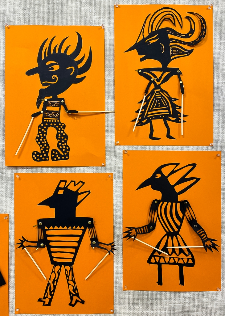 8th grade student's Wayang Kulit puppets (four in total). The puppets are made of black paper and set against a bright orange background to look like shadow puppets. They are intricately perforated to create elaborate patterns within the costume of each puppet, as well as to express each puppet's features. Their arms are joined with brass fasteners at the elbow and shoulder, manipulated at the hands by sticks