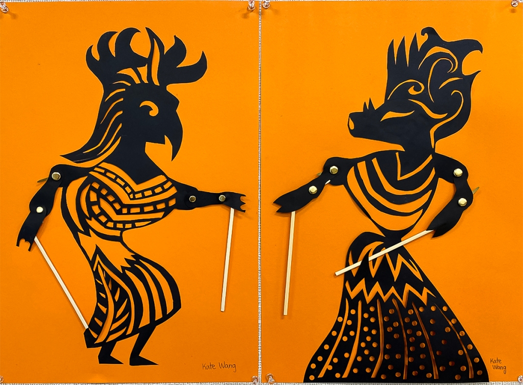 An 8th grade student's paired Wayang Kulit puppets. The puppets are made of black paper and set against a bright orange background to look like shadow puppets. They are intricately perforated to create elaborate patterns within the costume of each puppet, as well as to express each puppet's features. Their arms are joined with brass fasteners at the elbow and shoulder, manipulated at the hands by sticks.